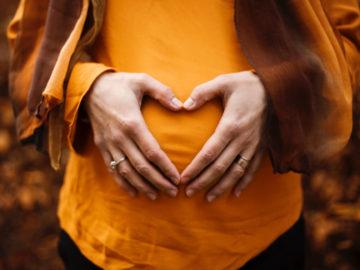 Ventre femme enceinte avec ses mains en forme de cœur