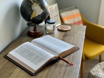 Bible posée sur une table avec un globe à côté
